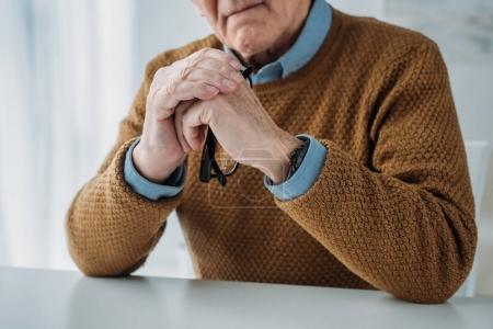 Photo for Serious senior thoughtful man sitting by the desk in light room - Royalty Free Image