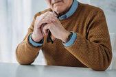 """Постер, картина, фотообои """"Серьёзный старший вдумчивый человек, сидя на столе в светлой комнате"""""""