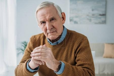 Senior thoughtful man sitting by the desk in light room