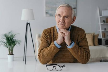 Photo for Senior thoughtful man sitting by the desk in light room - Royalty Free Image