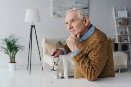 Senior confident man sitting by the desk in light room