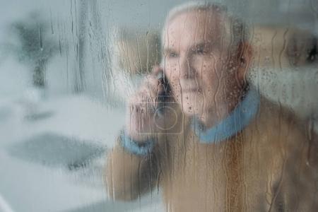 Photo pour Derrière la vue en verre pluvieux de l'homme dérangé âgé faisant un appel téléphonique - image libre de droit