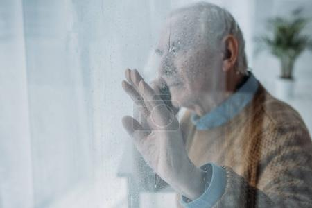 Photo for Behind the glass view of senior man making a phone call - Royalty Free Image