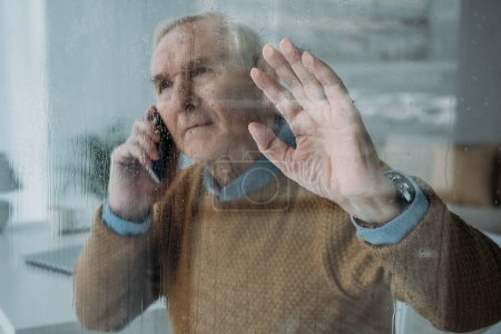 Behind the glass view of senior man making a phone call