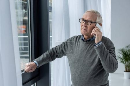 Senior confident man in eyeglasses making a phone call