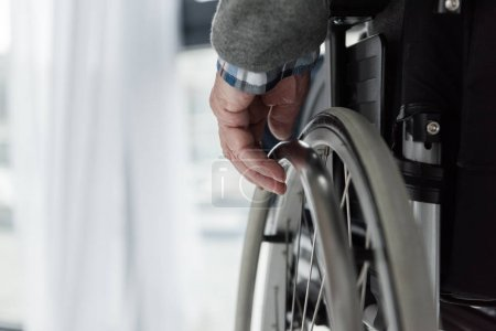 Close-up view of senior man hand on wheel of wheelchair