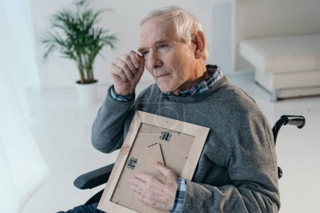 Senior man feels nostalgic while holding photo in frame