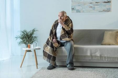 Sick senior man covered in plaid coughs while sitting sofa in room with medications on table