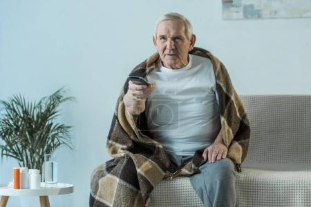 Sick senior man covered in plaid watches tv in room with medications on table