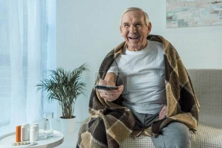 Photo for Senior man covered in plaid watches tv during sickness in room with medications on table - Royalty Free Image
