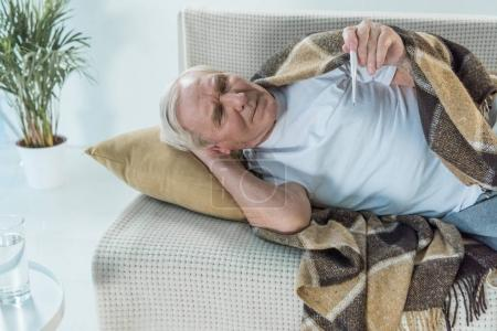 Senior sick man covered in plaid lies on sofa and checks thermometer