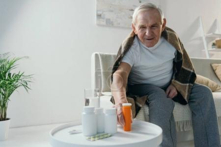 Senior sick man covered in plaid takes medications from table