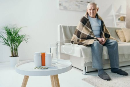 Senior chilled man covered in plaid looks at medications on table
