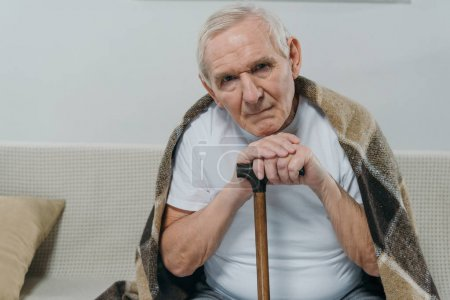 Senior man wearing plaid leans on a cane while sitting on sofa