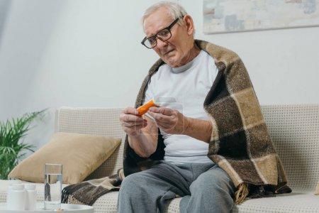 Senior man in eyeglasses and plaid looks at pill bottle