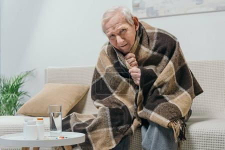 Senior chilled man covered in plaid with medications on table