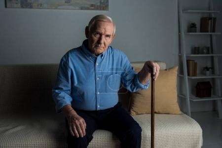 Photo for Senior confident man leans on a cane while sitting on sofa - Royalty Free Image