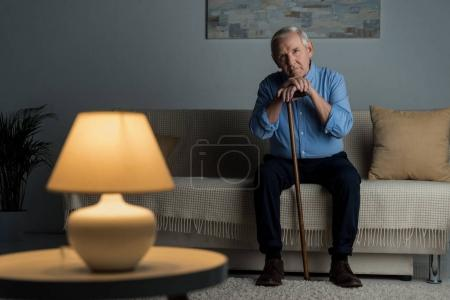 Tired senior man leans on a cane while sitting on sofa