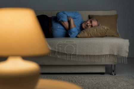 Photo pour Senior homme fatigué dort sur un canapé dans le salon - image libre de droit