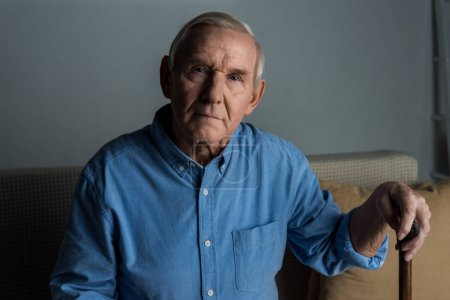 Senior confident man leans on a cane while sitting on sofa