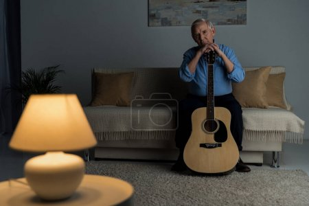 Senior confident man holds acoustic guitar while sitting on sofa in room
