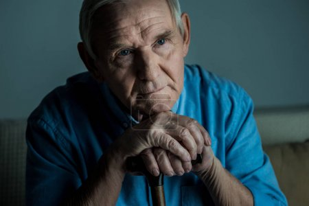 Photo for Tired senior man leans on a cane while sitting on sofa - Royalty Free Image