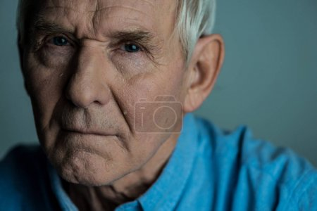 Senior man with sad expression cries looking at camera
