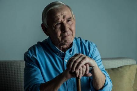 Senior sad man leans on a cane while sitting on sofa