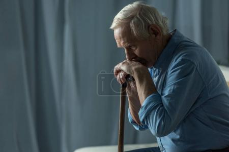 Photo for Senior sad man leans on a cane while sitting on sofa - Royalty Free Image