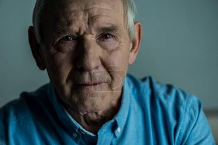 Senior man with sad expression cries looking at camera