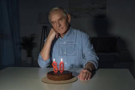 Photo pour Homme âgé célébrant 80 anniversaire seul avec gâteau et bougies numéro brûlant - image libre de droit