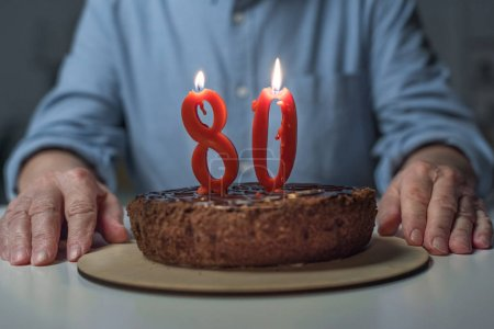 Close-up view of senior man celebrating 80 anniversary with cake and burning number candles