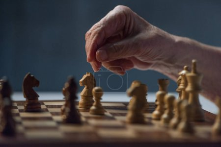 Close-up view of senior man playing chess board game