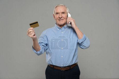 Confident senior man talking on phone and holding credit card isolated on gray background