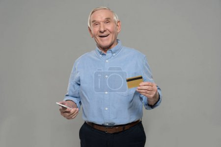 Senior man holds smartphone and credit card isolated on gray background isolated on gray background