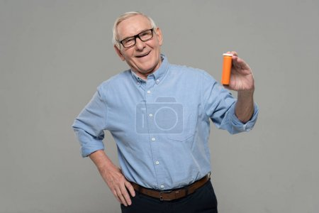 Confident senior man holds blank bottle of pills isolated on gray background