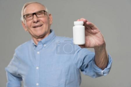 Photo pour Senior confiant homme tient bouteille blanche de pilules isolées sur fond gris - image libre de droit