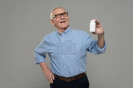 Senior smiling man holds white bottle of pills isolated on gray background