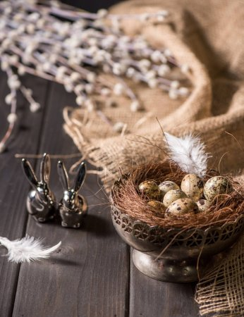 Photo for Close-up view of easter bunnies and quail eggs with nest in silver bowl for Easter holiday - Royalty Free Image