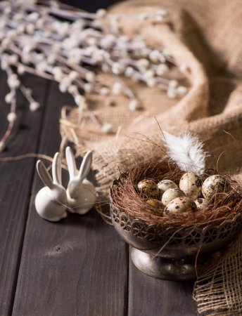 Photo for Close-up view of decorative easter bunnies and quail eggs with nest and feather in silver bowl for Easter holiday celebration - Royalty Free Image