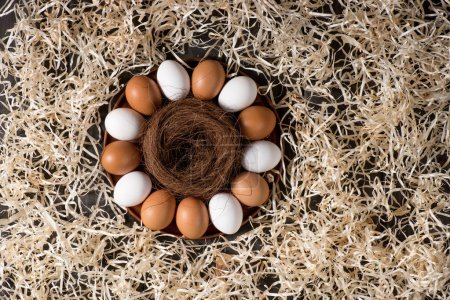 Photo pour Top view of chicken eggs and nest on plate and decorative shavings for Easter holiday - image libre de droit