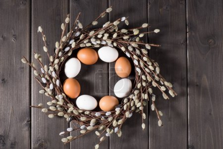 Photo for Top view of Easter composition with chicken eggs in catkins wreath on rustic wooden planks - Royalty Free Image