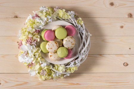 Photo pour Top view of Easter holiday composition with delicious macarons in plate and decorative flowers on wooden planks - image libre de droit