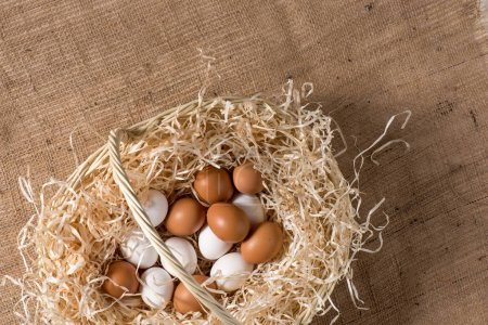 Photo pour Top view of white and brown chicken eggs in basket on sackcloth for Easter holiday - image libre de droit