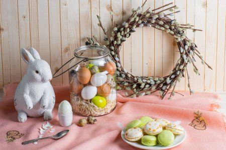 Photo for Colorful Easter eggs in jar, tasty macarons, catkins wreath and Easter bunny on table - Royalty Free Image