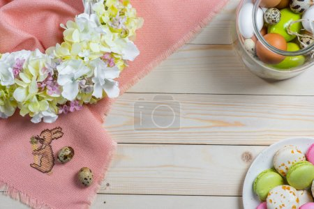 Photo for Colorful Easter eggs, tasty macarons, floral wreath and pink fabric on table - Royalty Free Image
