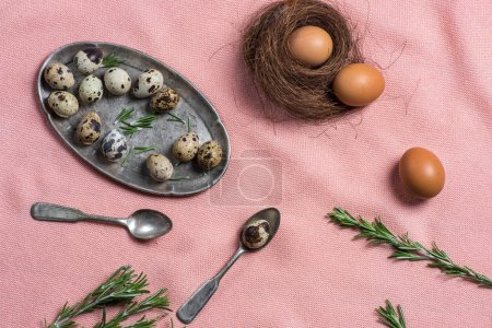 Photo for Chicken and quail eggs, rosemary and old silver cutlery on pink fabric for Easter - Royalty Free Image