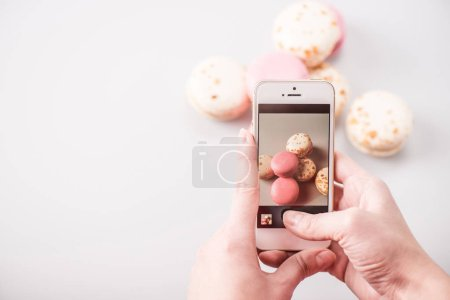 Photo for Close-up view of human hands photographing macarons with smartphone - Royalty Free Image