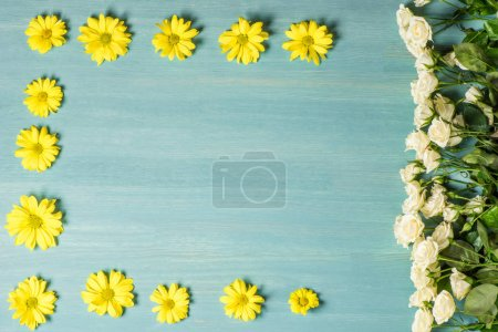 Photo pour Top view of beautiful white roses and yellow flowers on blue for Mother's day - image libre de droit