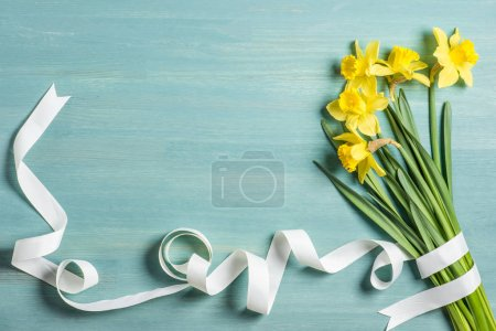 Photo for Top view of beautiful yellow daffodils and ribbon on blue for gift on Mother's day holiday - Royalty Free Image